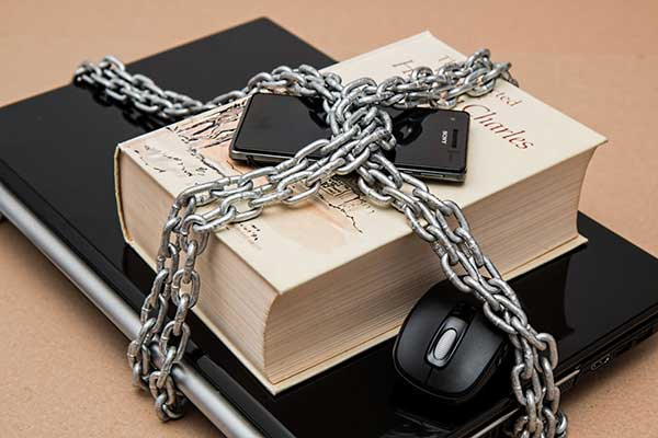 Laptop phone and book locked in a chain